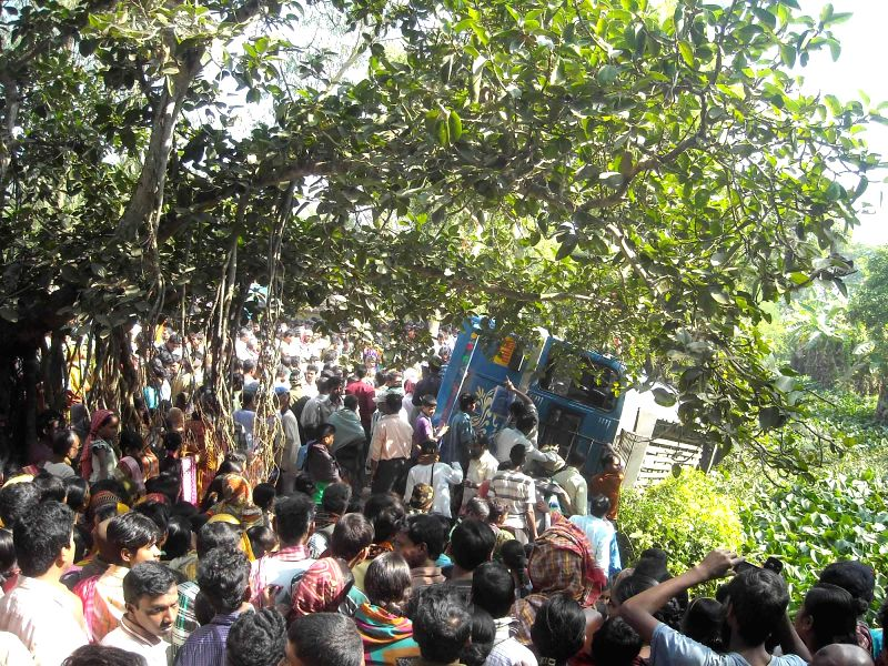 South 24 Parganas: People gather at the site where a bus fell into a canal in West Bengal's South 24 Parganas district on Dec 14, 2014. Three people were killed and at least 18 others injured in the .