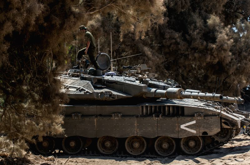 An Israeli soldier walks on a Merkava tank in southern Israel bordering the Gaza Strip, on Aug. 6, 2014. Israel has agreed to extend the ongoing ceasefire in ...