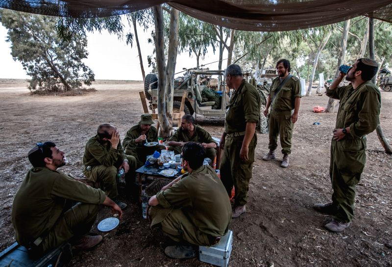 Israeli soldiers have their brunch in southern Israel bordering the Gaza Strip, on Aug. 6, 2014. Israel has agreed to extend the ongoing ceasefire in the Gaza ..