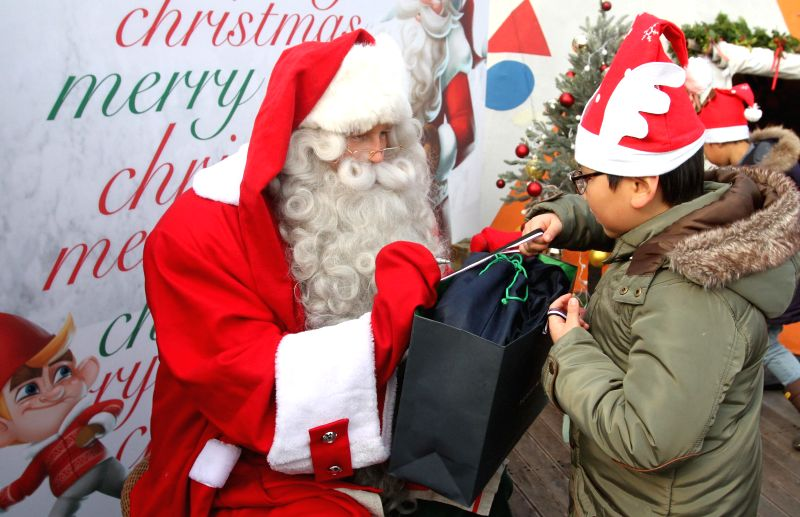 South Korea: Santa Claus presents gifts to a kid in Seoul, South Korea, Dec. 12, 2014. Santa Claus from Rovaniemi of Finland, the official hometown of Santa Claus, came to South Korea to fulfill the .