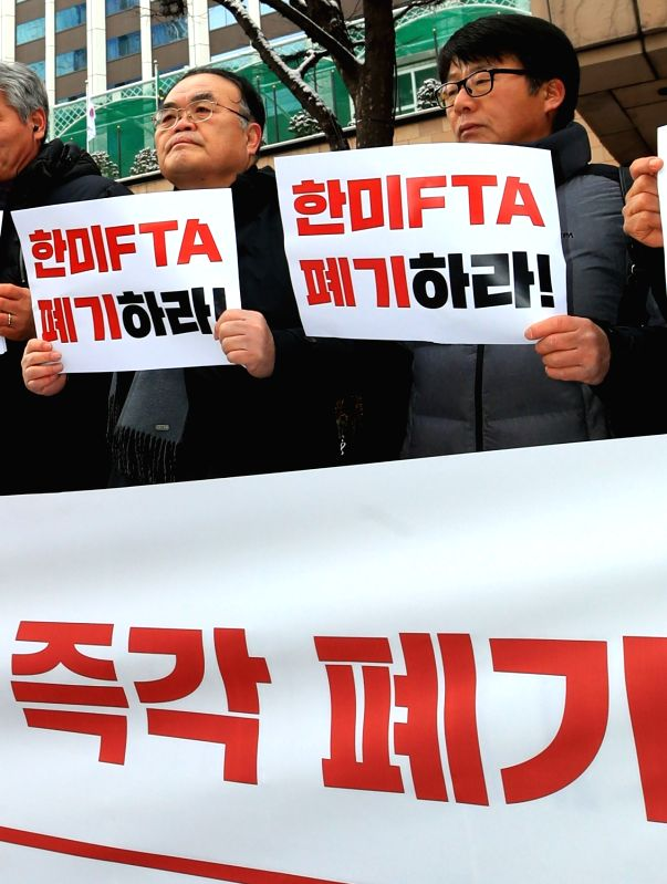 South Korean activists hold a rally calling for the abolition of the free trade deal between South Korea and the United States in front of Lotte Hotel in Seoul on Jan. 31, 2018. Negotiators ...