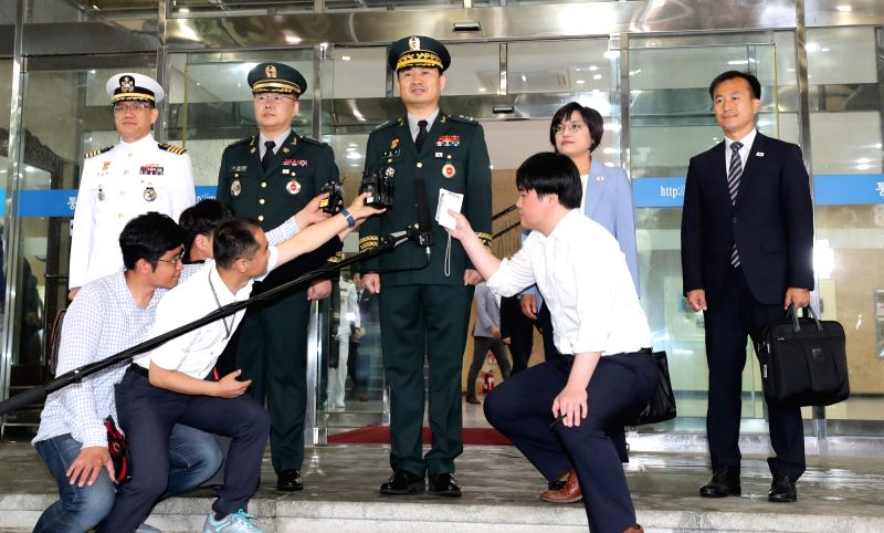 South Korean delegates speak to reporters as they leave Seoul on June 14, 2018, for the truce village of Panmunjom for the first high-level inter-Korean military talks in more than 10 ...