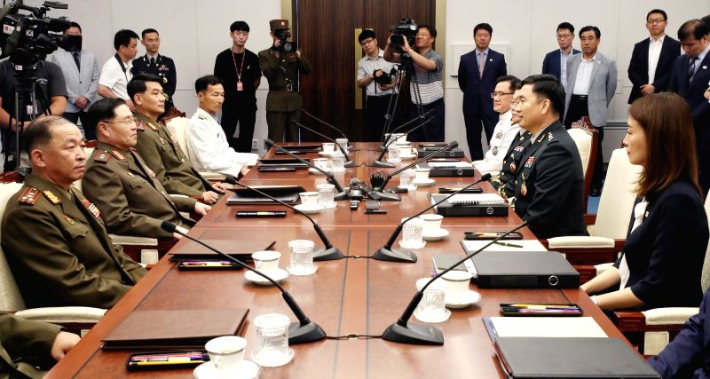South Korean military officials, seated on the right side, and their North Korean counterparts start inter-Korean military talks at the truce village of Panmunjom on July 31, 2018. It is ...