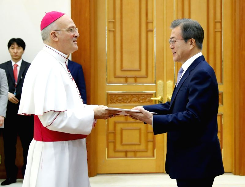 South Korean President Moon Jae-in (R) receives credentials from new Vatican Ambassador to South Korea Alfred Xuereb at the presidential office Cheong Wa Dae in Seoul on July 25, 2018.