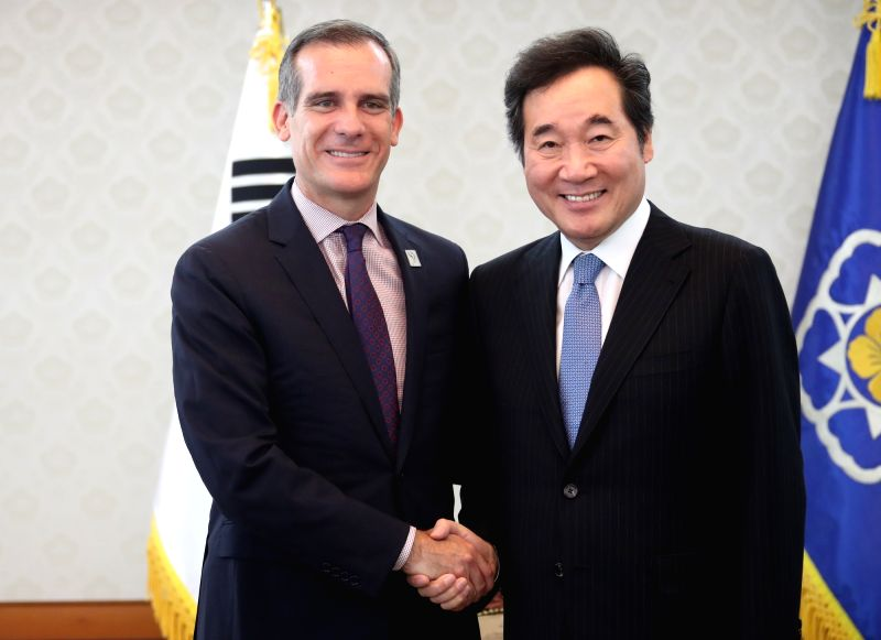South Korean Prime Minister Lee Nak-yon (R) poses for a photo with Los Angeles Mayor Eric Garcetti during their meeting at the government complex in Seoul on July 27, 2018. - Lee Nak