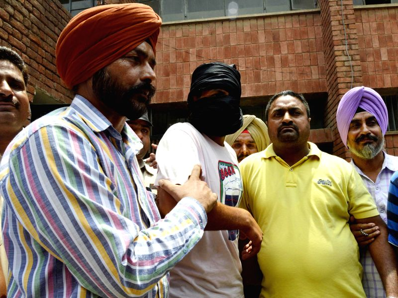 Special Operation Cell officials take a person who was allegedly apprehended with 5 kg of heroin worth Rs. 25 crores in international market in Amritsar on July 8, 2014.