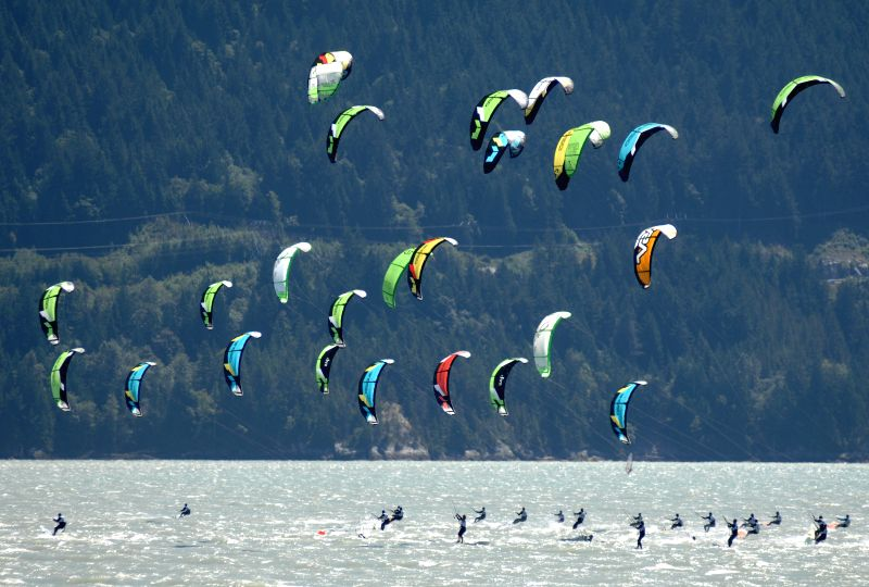 Athletes race during the opening day of 2014 West Coast Open International Kiteboarding Championship in Squamish, Canada, July 18, 2014. (Xinhua/Sergei ...
