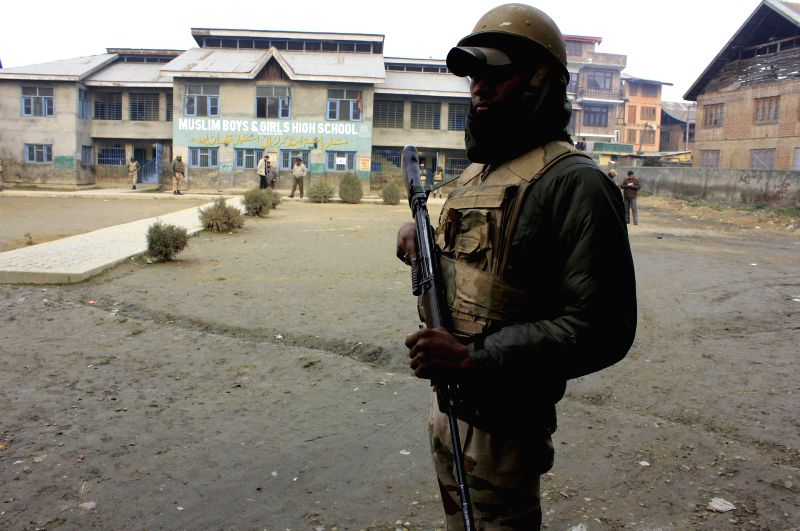 A soldier stands guard at a deserted polling booth in Habba Kadal constituency of Srinagar during the fourth phase of  on Dec 14, 2014.