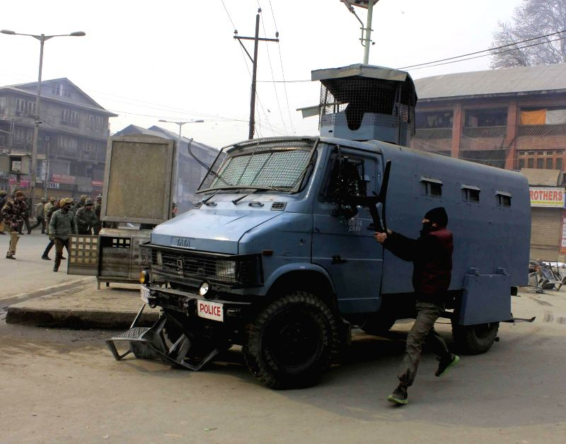 An alleged Jammu and Kashmir Liberation Front (JKLF) worker smashes windows of a police vehicle in Srinagar on Dec 24, 2014.
