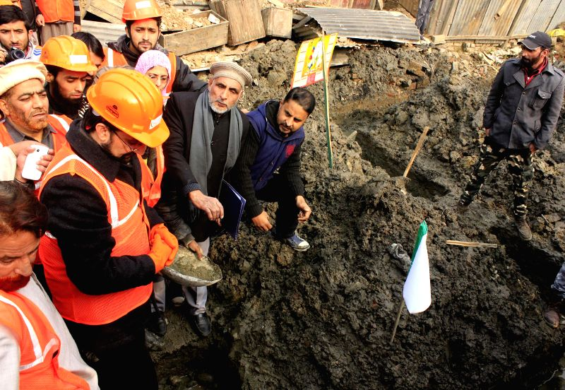 Chairman of Hurriyat Conference, Mirwaiz Umar Farooq laying foundation stone of houses being rebuild which were washed away in recent floods in Srinagar on Nov. 29, 2014.
