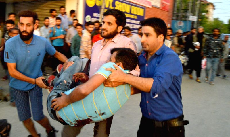 ": Srinagar: One of the guards of senior journalist and Editor-in-Chief of English daily ""Rising Kashmir"" Shujat Bhukhari being taken for treatment in Srinagar, on June 14, 2018. Bhukhari was shot ..."