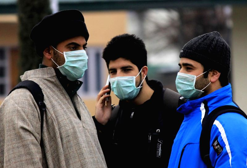 People wear masks as a protective measure against swine flu in Srinagar, on Feb 22, 2015.