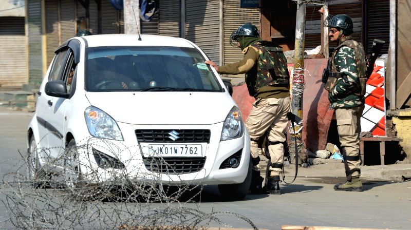 :Srinagar: Police conducts security checks after restrictions were imposed to prevent separatist-called protests against the death of two civilians in army firing; in Srinagar on Jan 28, 2018. Two ...