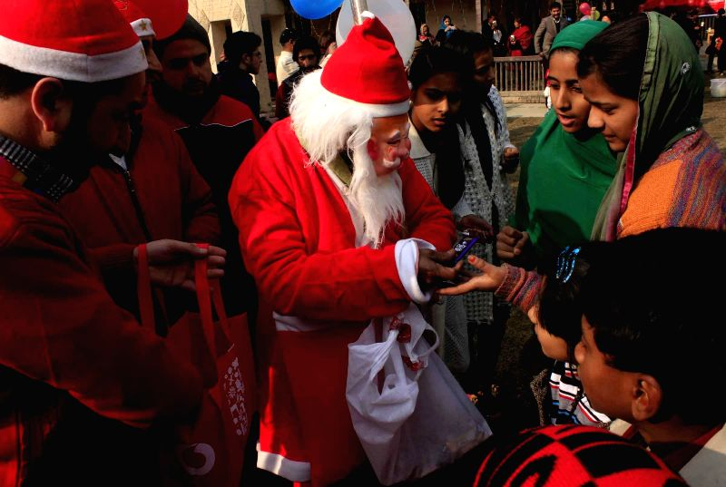 Santa Claus distributes chocolates to children outside a church on Christmas in Srinagar, on Dec 25, 2014.