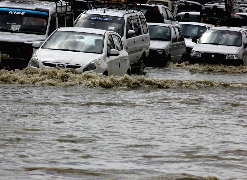 Vehicles ply on waterlogged streets of Srinagar as water level in Jhelum river  crosses danger mark on March 30, 2015. Authorities Monday declared flood in the Kashmir Valley, asking people ...