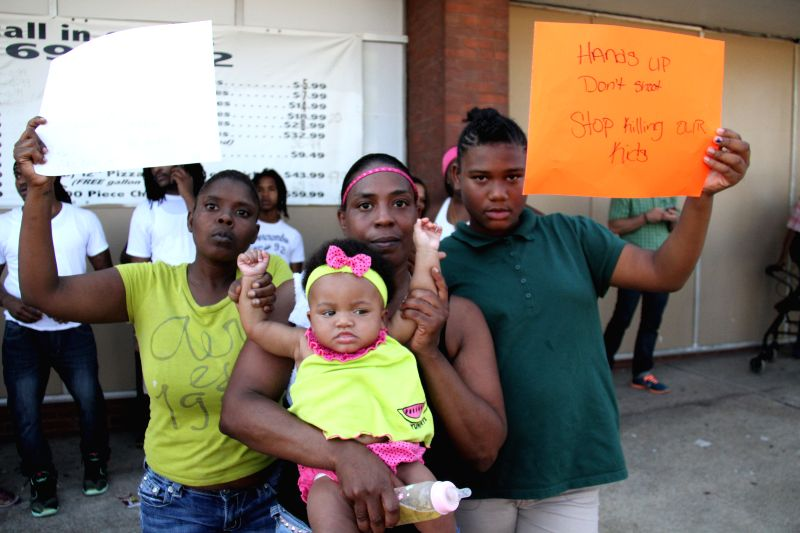 ST.People protest at the site where a 23-year-old black male was shot and killed by two police officers in northern St. Louis, Missouri, the United States, Aug. 19, .