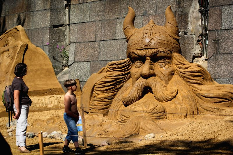 ST.Visitors walk past sand sculptures displayed during the international festival of sand sculptures in St.Petersburg, Russia, on July 17, 2014. (Xinhua/IANS) ..