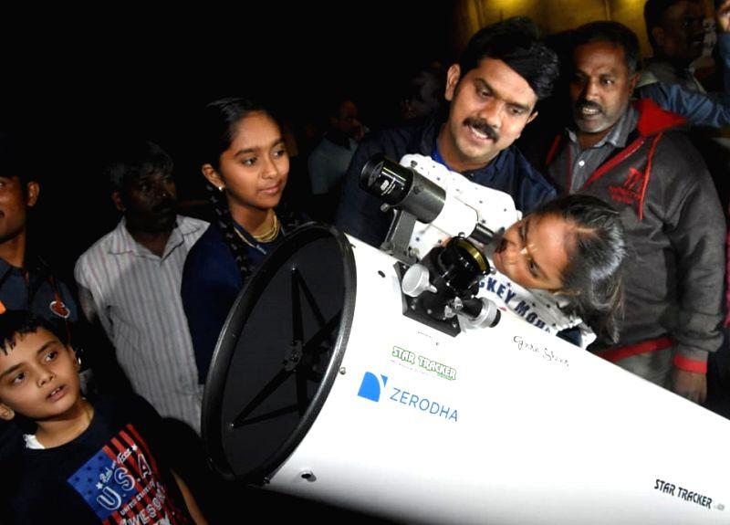 Stargazers use a telescope to observe lunar eclipse at Jawaharlal Nehru Planetarium in Bengaluru on July 27,  2018.