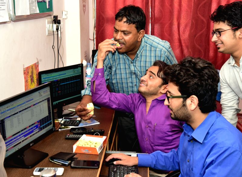 Stock brokers celebrate as BSE Sensex and the NSE Nifty touched fresh record highs of 31,000 and 9,600 points mark respectively in Bikaner on May 26, 2017.