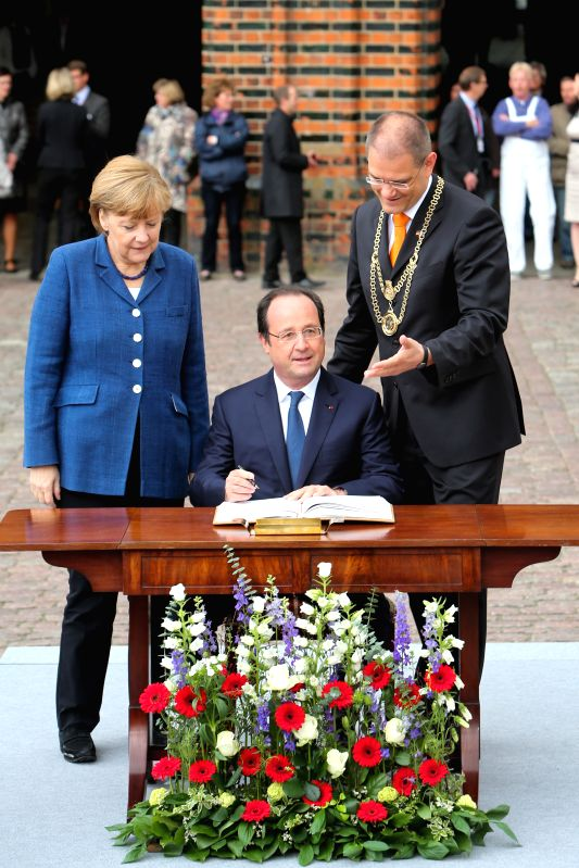STRALSUND (GERMANY), May 10, 2014 German Chancellor Angela Merkel (1st L) waits while visiting French President Francois Hollande autographs the city's guest book in the Baltic coastal ...