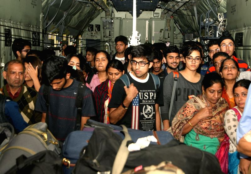 Stranded people who were airlifted from Tambaram air base, near Chennai following heavy rains, de-board an Indian Air Force aircraft at Air Force Station, Palam, in New Delhi on Dec 3, ...