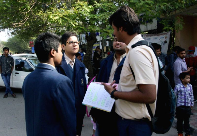 Students carry out last minute revisions outside an examination centre ahead of their board examinations in New Delhi on March 20, 2015.