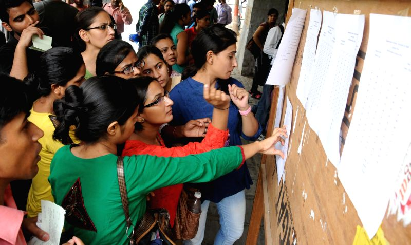 Students check cut-off list at North Campus of Delhi University in New Delhi on July 1, 2014.