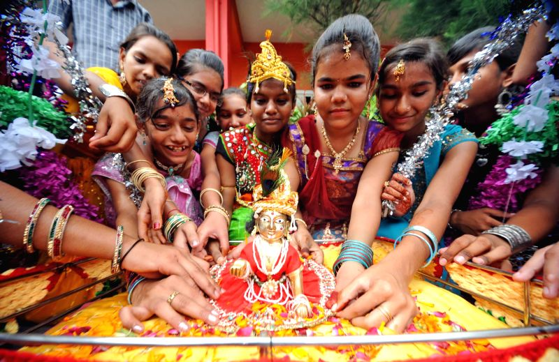Students hold an idol of Lord Krishna at their school on the eve Janmashtami festival in Ahmedabad Aug 16, 2014.