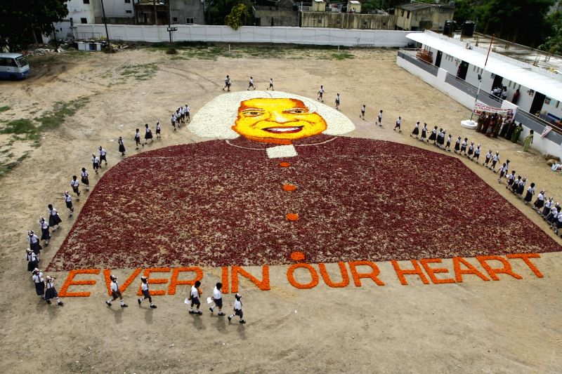 Students of a Chennai school stand in a formation to make a portrait made of flowers depicting the image of former Indian President APJ Abdul Kalam on the eve of his death anniversary in ...
