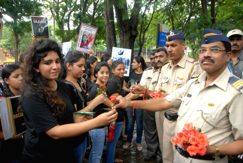 Students of Khalsa College tie rakhi on the wrist of Mumbai Police constables in Mumbai on Aug. 9, 2014.