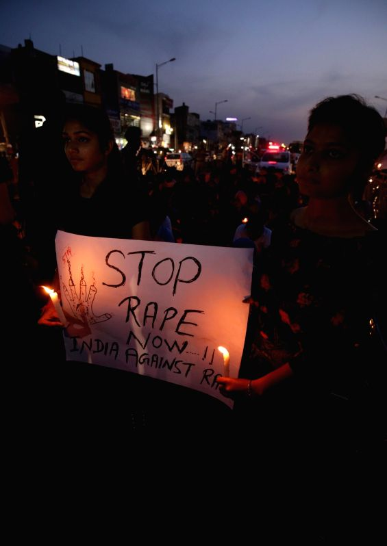 Students participate in a candle light vigil organised to express solidarity with Kathua rape and murder victim, in Amritsar on April 14, 2018.