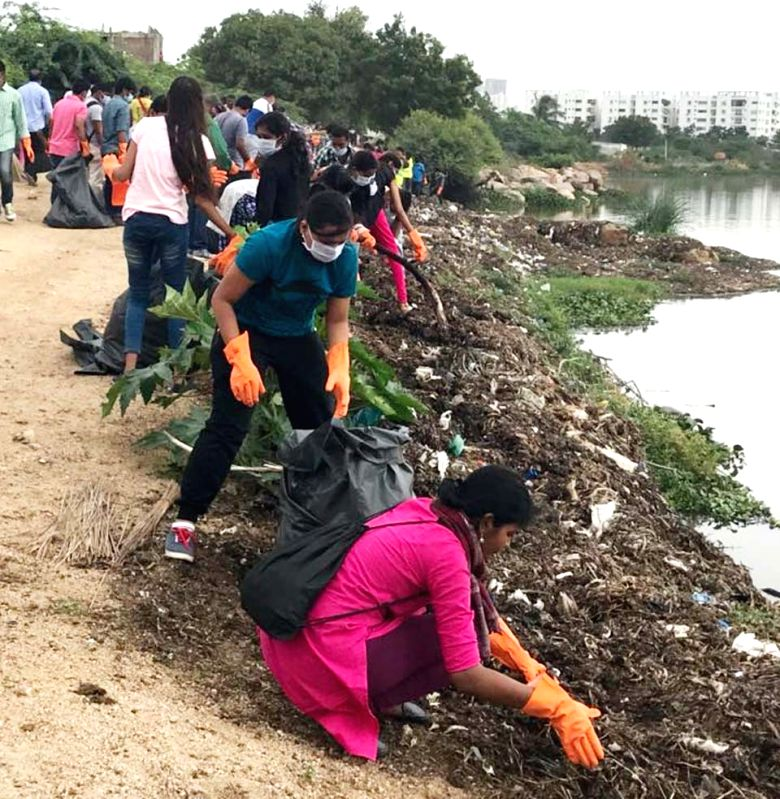 Students participate in a Greater Hyderabad Municipal Corporation (GHMC) cleanliness drive at the banks of Hussain Sagar lake, in Hyderabad on July 30, 2018.