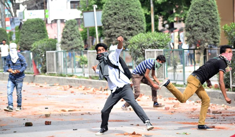 Students pelt stone on security personnel during a protest in Srinagar on May 9, 2017.
