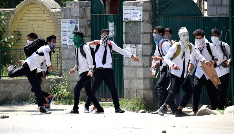 Students pelt stones on security personnel in Srinagar on May 23, 2017.