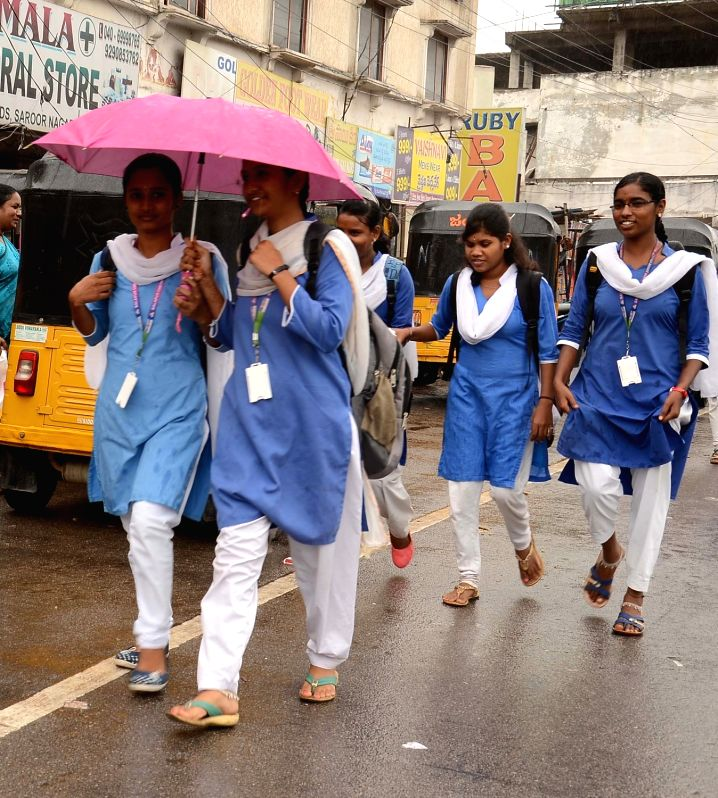 Students shield themselves with umbrellas during rains, in Hyderabad on July 12, 2018.
