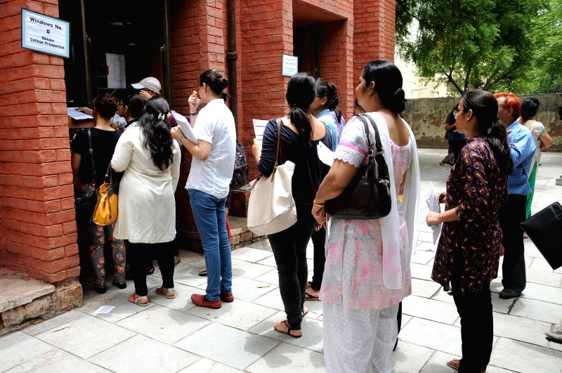 Students stand in a queue to submit admission forms at a Delhi University college in New Delhi on July 1, 2014.