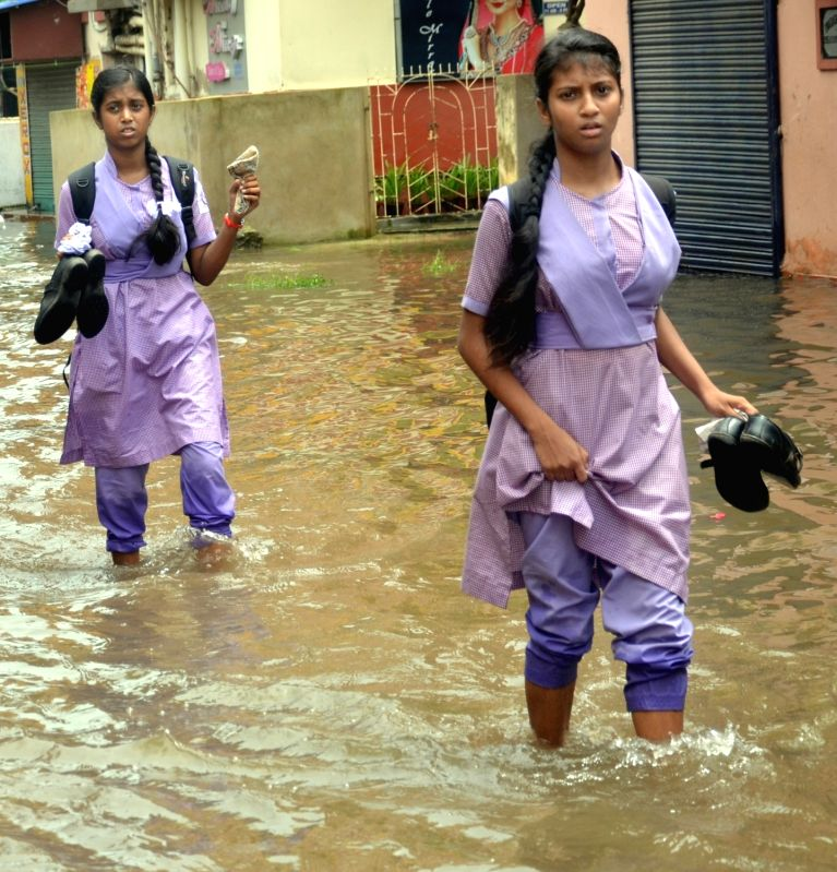Students struggle through a waterlogged street after heavy rains lashed Kolkata, on July 23, 2018.