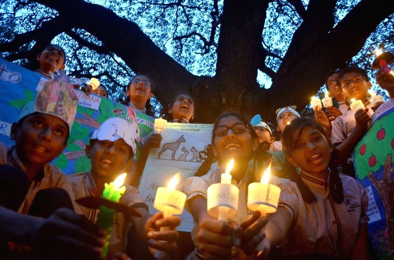 Students take out a candlelight vigil during an awareness programme to 'Save Trees' in Bengaluru on June 7, 2017.