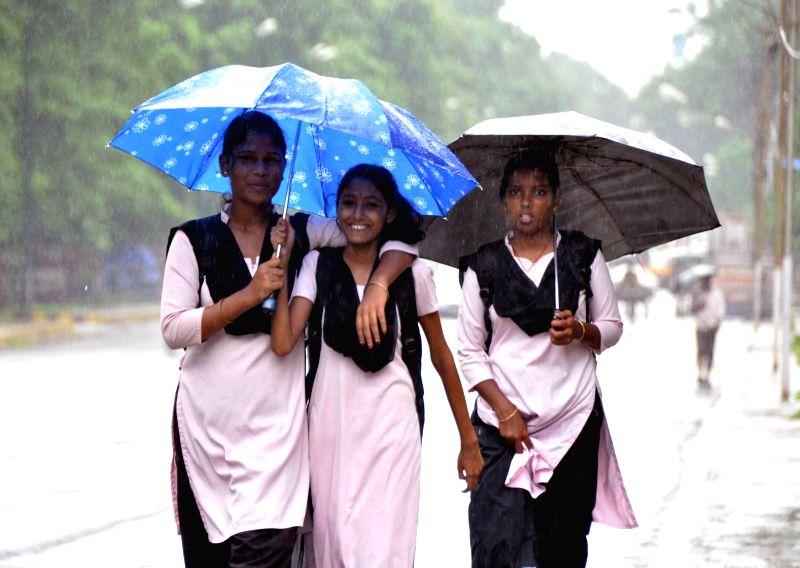 Students use umbrellas to shield themselves from rain in Bhubaneswar on July 19, 2014. (Photo : Arabinda Mahapatra/IANS)