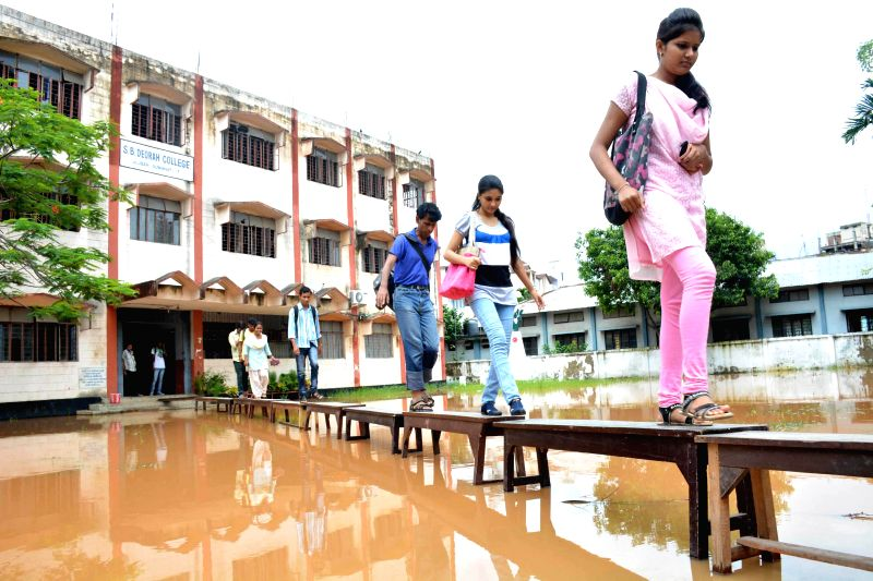 Students walk on benches to enter their flooded college in Guwahati on June 27, 2014.