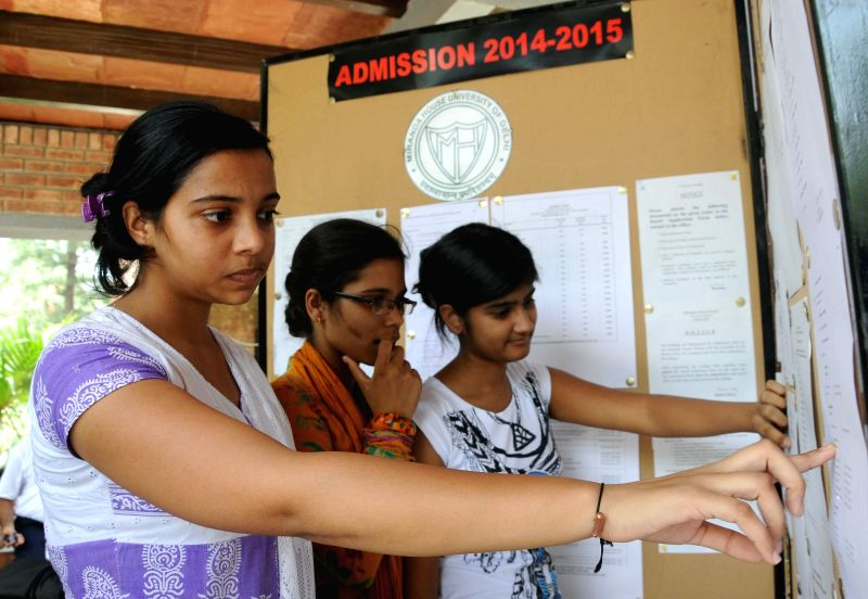 Students who have applied for admissions to various under-graduate courses of Delhi University check the 3rd cut-off list at Miranda House in New Delhi on July 8, 2014.