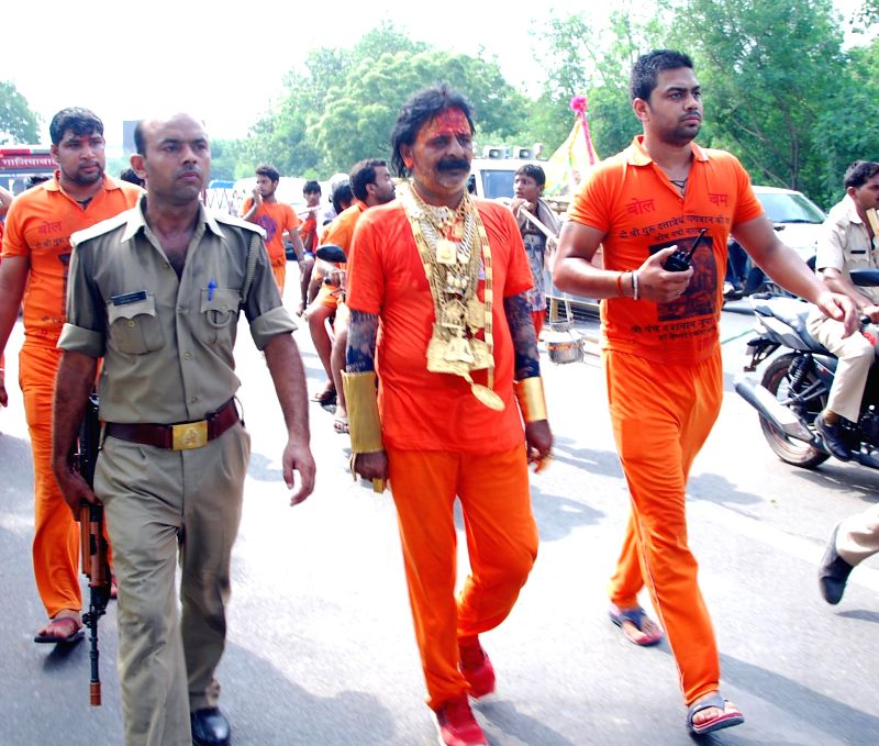 Sudhir Kumar also known as 'Golden Baba' who is allegedly wearing 8.5 kg gold ornaments and a watch worth 27 lakhs passes through Ghaziabad amidst tight security on July 22, 2014. Kumar is returning . - Sudhir Kumar