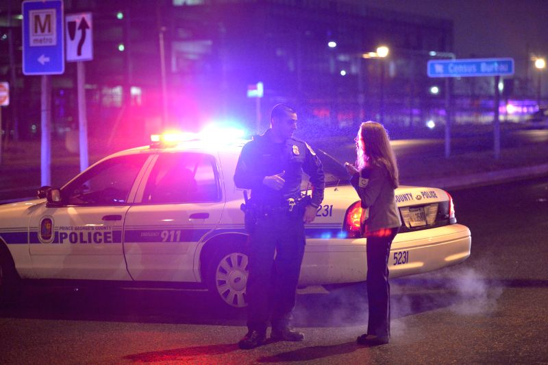 A journalist talks to a policeman at the street beside the U.S. Census Bureau headquarters after shooting happened at the bureau in Suitland, Maryland, the United ...