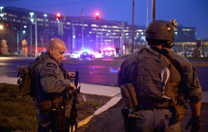 A policeman walks across the street beside the U.S. Census Bureau headquarters after shooting happened at the bureau in Suitland, Maryland, the United States, ...