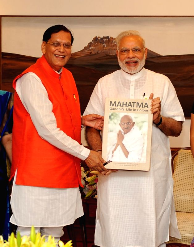 Sulabh International Founder presenting the first copy of book on Mahatma Gandhi?s life to Prime Minister Narendra Modi at his official residence.