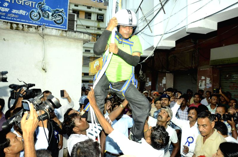 Suman Kumar who is physically challenged attempts to climb down a 70 metre high building using a rope in Patna on Aug 31, 2014. - Suman Kumar