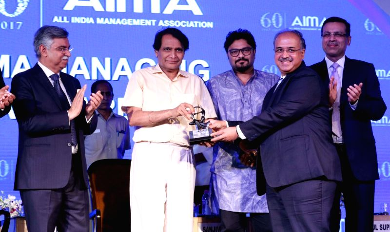 Sun Pharma founder Dilip Sanghvi receives Entrepreneur Of The Year Award from Union Railway Minister Suresh Prabhu at the AIMA Awards ceremony in New Delhi, on April 27, 2017. - Suresh Prabhu