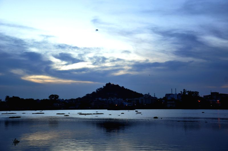 Sun sets as clouds hover on a Ranchi lake on June 27, 2015.