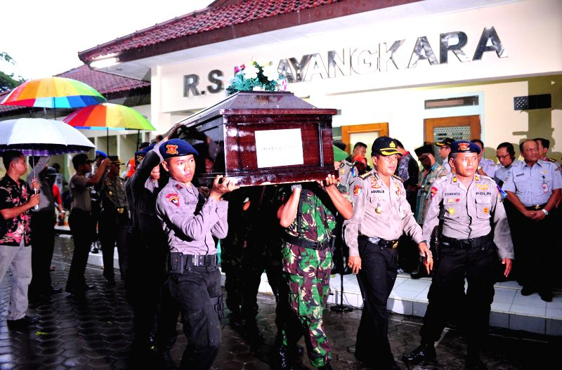 Indonesian police carry a coffin of Hayati Lutfiah, one of the victims of AirAsia flight QZ8501 after handing it over to his family at Bhayangkara Hospital in ...