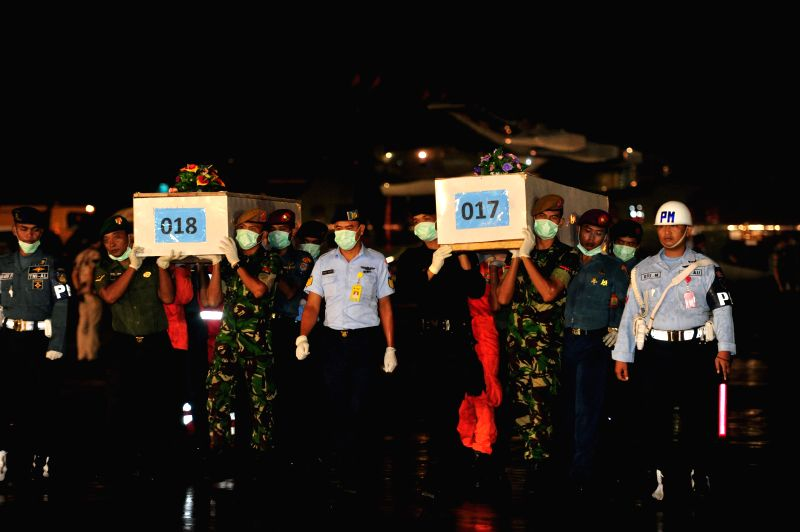 Indonesian soldiers carry coffins containing victims of AirAsia flight QZ8501 at Juanda Naval Air Base in Surabaya, Indonesia, Jan. 2, 2015.?